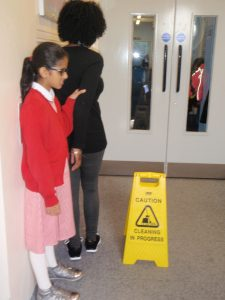 Photo demonstrating navigating around a narrow space - The guide and the child are walking past a free-standing Caution sign.
